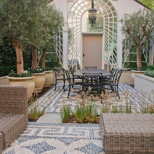 Inspiration for a medium sized mediterranean back patio in Hertfordshire with no cover and a potted garden.