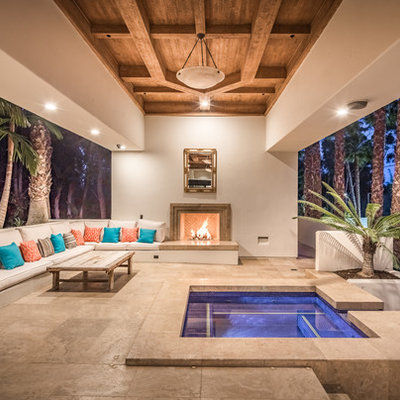 Example of a huge trendy backyard tile patio design in San Diego with a roof extension and a fireplace