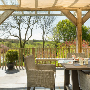 Design ideas for a large rural back patio in Devon with tiled flooring and an awning.
