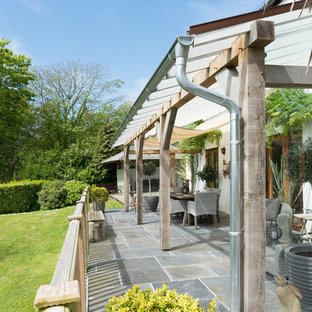 Photo of a large country back patio in Devon with tiled flooring and an awning.