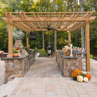 Esempio di un grande patio o portico tradizionale dietro casa con pavimentazioni in cemento e una pergola