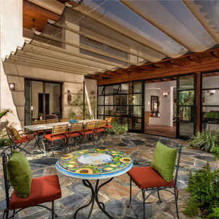 Patio - mediterranean stone patio idea in Orange County with an awning