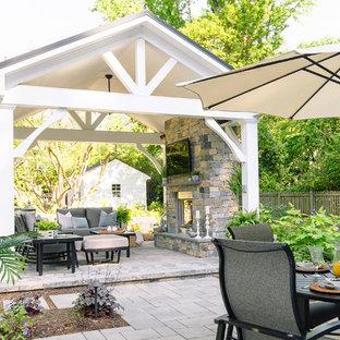 Imagen de patio clásico, grande, en patio trasero, con chimenea, adoquines de hormigón y cenador