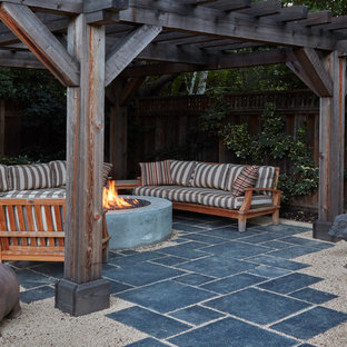 Idee per un piccolo patio o portico american style dietro casa con pavimentazioni in pietra naturale e una pergola