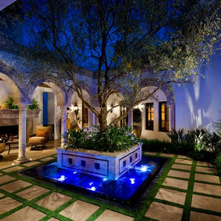Design ideas for a mediterranean courtyard patio in Orange County with a water feature.