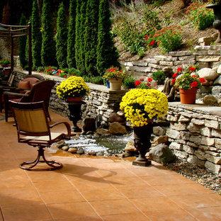 Ispirazione per un grande patio o portico eclettico dietro casa con fontane, cemento stampato e un gazebo o capanno