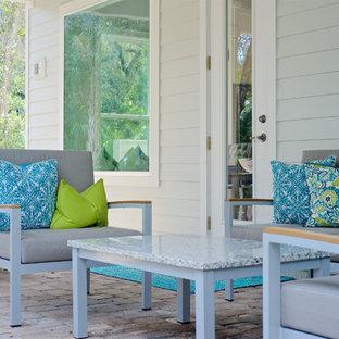 Ispirazione per un patio o portico chic dietro casa con pavimentazioni in mattoni e un tetto a sbalzo