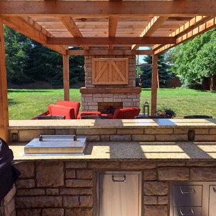 Idee per un grande patio o portico country dietro casa con un focolare, pavimentazioni in cemento e una pergola