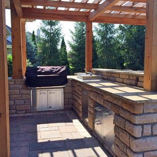Esempio di un grande patio o portico country dietro casa con un focolare, pavimentazioni in cemento e una pergola