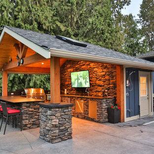 Foto di un ampio patio o portico stile americano dietro casa con lastre di cemento e un tetto a sbalzo