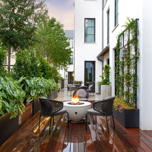 Example of a transitional backyard patio design in Dallas with a fire pit and decking