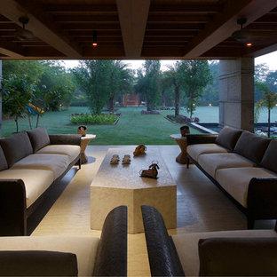 Idéer för att renovera en stor funkis uteplats på baksidan av huset, med en fontän, granitkomposit och takförlängning