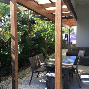 Foto di un piccolo patio o portico tropicale dietro casa con graniglia di granito e una pergola