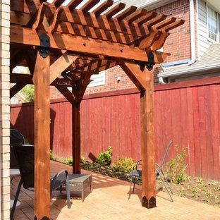 Immagine di un patio o portico stile rurale di medie dimensioni e nel cortile laterale con cemento stampato e una pergola