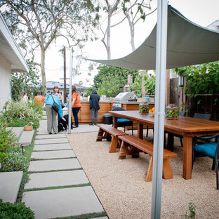 Photo of a large modern side patio in Los Angeles with gravel, an outdoor kitchen and an awning.