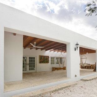 Aménagement d'une terrasse exotique avec une extension de toiture.