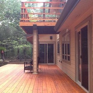 Esempio di un grande patio o portico rustico dietro casa con pedane e un tetto a sbalzo