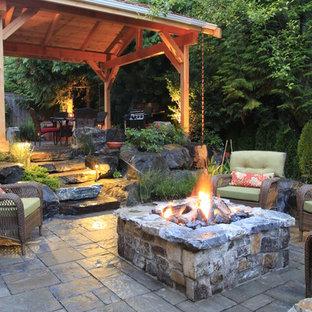 Cette image montre une terrasse arrière traditionnelle de taille moyenne avec un foyer extérieur, un gazebo ou pavillon et des pavés en pierre naturelle.