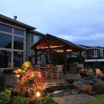 Inspiration for a mid-sized timeless backyard stone patio remodel in Seattle with a pergola