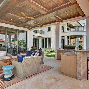Foto di un ampio patio o portico classico dietro casa con pavimentazioni in pietra naturale e un tetto a sbalzo