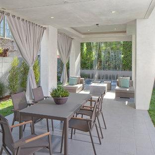 Exemple d'une grande terrasse arrière tendance avec un point d'eau, du carrelage et une extension de toiture.