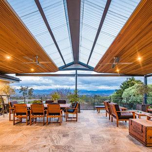 Réalisation d'une terrasse design avec du carrelage et une pergola.