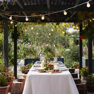 Diseño de patio rústico, en patio trasero, con gravilla y pérgola