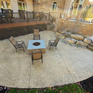 Ispirazione per un grande patio o portico chic davanti casa con un focolare e cemento stampato