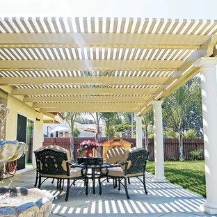Ispirazione per un patio o portico chic di medie dimensioni e dietro casa con pavimentazioni in cemento, una pergola e fontane
