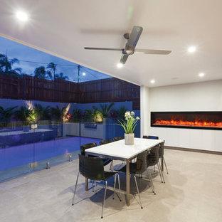 Idee per un grande patio o portico contemporaneo dietro casa con un focolare, cemento stampato e un tetto a sbalzo