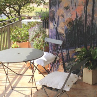 Design ideas for a small nautical front patio in Sydney with natural stone paving, a potted garden and an awning.