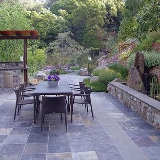 Ispirazione per un ampio patio o portico contemporaneo dietro casa con piastrelle e una pergola