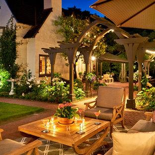 Foto di un ampio patio o portico chic dietro casa con un focolare, pavimentazioni in mattoni e una pergola
