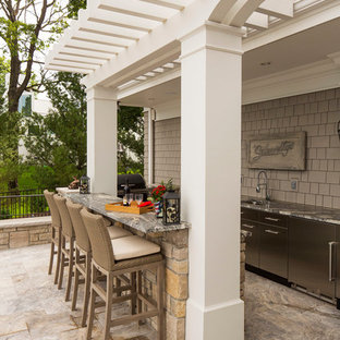 Patio kitchen - large traditional backyard patio kitchen idea in Minneapolis with a pergola