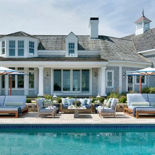 Ispirazione per un grande patio o portico stile marino dietro casa con piastrelle e una pergola
