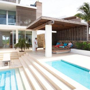 Foto di un grande patio o portico tropicale dietro casa con una pergola