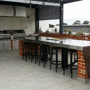 Esempio di un grande patio o portico stile shabby in cortile con piastrelle e un tetto a sbalzo