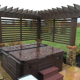 Foto på en liten funkis uteplats på baksidan av huset, med naturstensplattor och en pergola