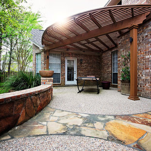Inspiration for a mid-sized timeless backyard stone patio kitchen remodel in Houston with a pergola
