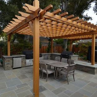 Exemple d'une terrasse avec une cuisine extérieure arrière chic de taille moyenne avec du carrelage et une pergola.