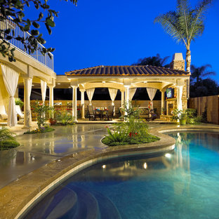 Inspiration for a large mediterranean back patio in Los Angeles with an outdoor kitchen, concrete slabs and a gazebo.