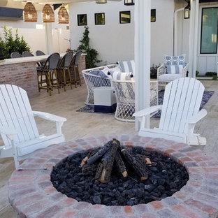 Foto di un patio o portico country di medie dimensioni e dietro casa con piastrelle e una pergola