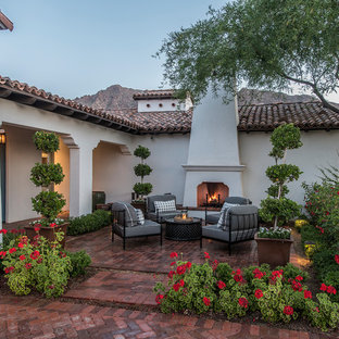 Example of a huge tuscan courtyard brick patio design in Phoenix with no cover and a fireplace