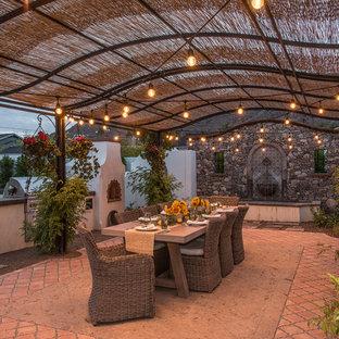Modelo de patio mediterráneo, extra grande, en patio trasero, con cocina exterior, pérgola y adoquines de ladrillo