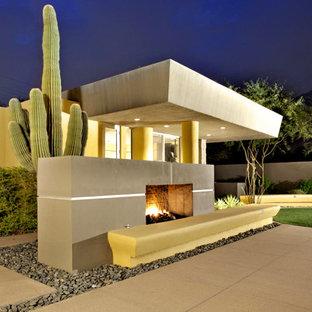 Immagine di un ampio patio o portico moderno dietro casa con un focolare, lastre di cemento e un tetto a sbalzo
