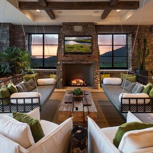 Esempio di un patio o portico american style con un tetto a sbalzo e un caminetto