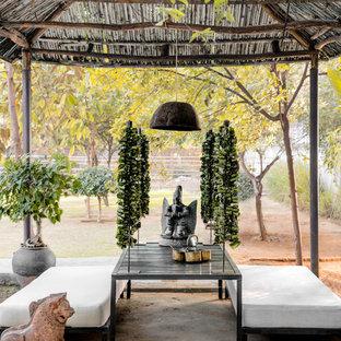 Ispirazione per un patio o portico etnico dietro casa con un gazebo o capanno