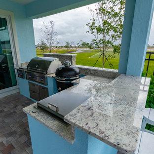 Immagine di un patio o portico tropicale dietro casa con pavimentazioni in mattoni e un tetto a sbalzo