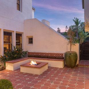 Пример оригинального дизайна: большой дворик на внутреннем дворе в средиземноморском стиле с местом для костра и покрытием из плитки без защиты от солнца