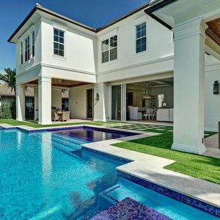 Esempio di un grande patio o portico tropicale dietro casa con un tetto a sbalzo e pavimentazioni in cemento